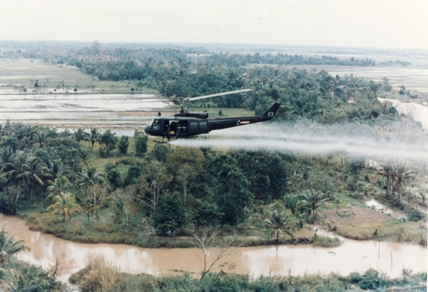 US Army helicopter spraying Agent Orange over Vietnam. Public Domain